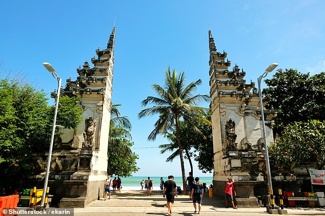 Tourists are seen walking to Kuta Beach through the traditional gate at beautiful sunny day