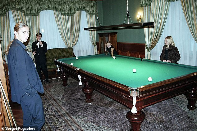 Ekaterina (right) watches as her sister Maria plays pool with Sergei Pugachev's son Alexander (second from left) and Viktor (left) in the Kremlin in the early 2000s