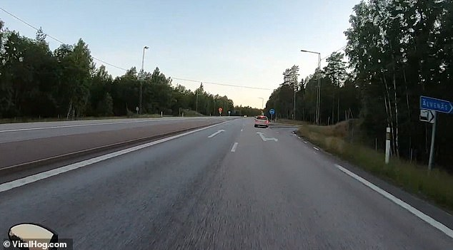Video footage has captured the terrifying moment a car almost knocks a motorcyclist off his bike after it spun out onto the motorway in Karlstad, Sweden last week