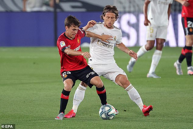 Real Madrid midfielder Luka Modric competes for possession with Aleix Febas of Mallorca