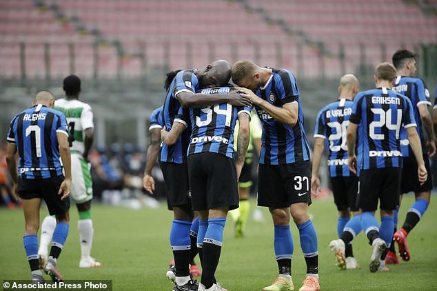 Inter Milan's Cristiano Biraghi, center, celebrates with his teammates Romelu Lukaku, left, and Skriniar after scoring his side's second goal during the Serie A soccer match between Inter Milan and Sassuolo at the San Siro Stadium, in Milan, Italy, Wednesday, June 24, 2020. (AP Photo/Luca Bruno)