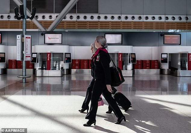 Air crew walk through the Qantas Terminal at Sydney Airport on June 19. 15,000 staff members already stood down will remain out of work 'for some time'