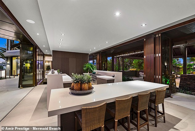 The open-plan kitchen (pictured), fitted with walnut cabinets, stone benchtops a hidden Butler's pantry with a large cold room