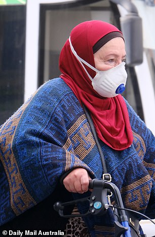 A Coburg local wears a protective face mask on Thursday amid news of the cluster