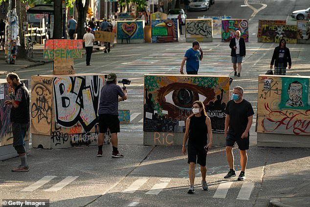 Pictured: People walk by barricades in the area known as the Capitol Hill Organized Protest (CHOP) on June 24, 2020 in Seattle, Washington