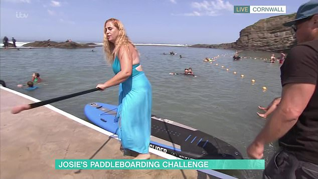 Off she goes: Looking fabulous in a bright blue swimsuit and sarong skirt, she managed to push herself off the dock successfully