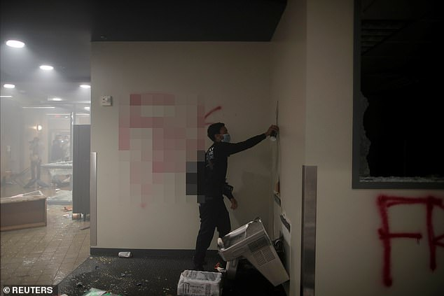 Chaos from inside the Minneapolis Police precinct on May 29 show people inside the building, vandalizing it with graffiti