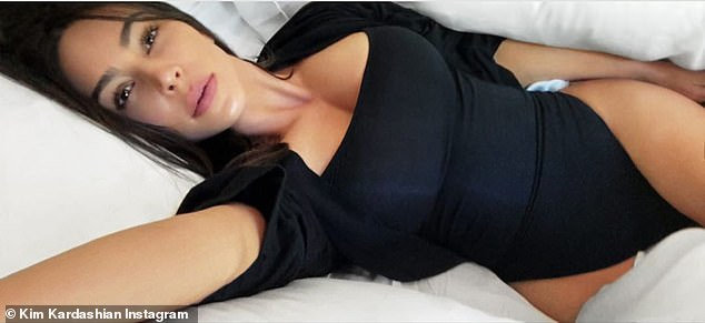 Comfortable:The mother of four then posed on her bed, with her ample cleavage and her hips on full display