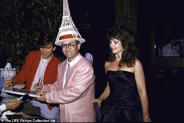 British singer/songwriter Elton John wears an Eiffel Tower hat as he signs an autograph with his then-wife