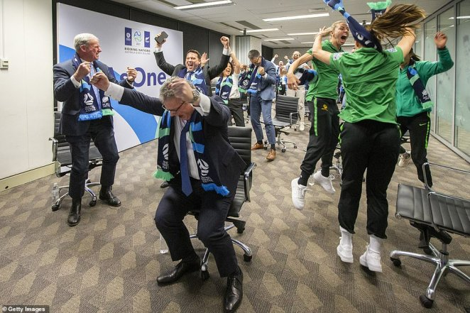 Chairman of Football Federation AustraliaChris Nikou (centre) throws his arms into the air as FIFA announces Australia and New Zealand will hostthe FIFA Women's World Cup 2023