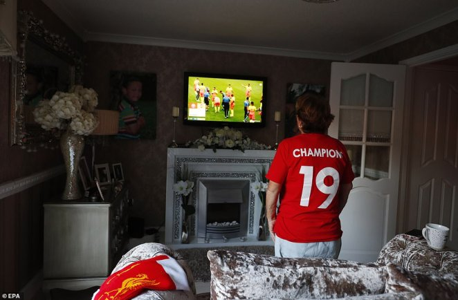 Liverpool supporter Emily Farley watches the Premier League match between Chelsea FC and Manchester City FC on a television screen inside her home in Liverpool