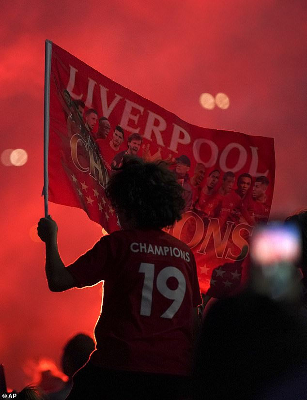 A young Liverpool fan holds a flag aloft with 'Champions 19' etched onto the back of their shirt