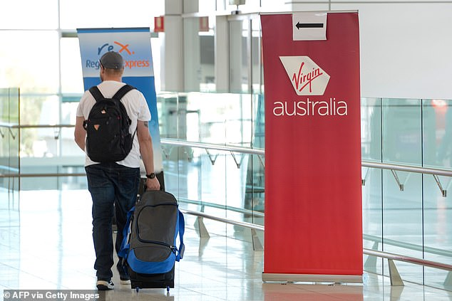 Virgin Australia airlines is likely to be bought by American private equity firm Bain Capital. Pictured is a traveller walking past a Virgin Australia sign at Adelaide airport
