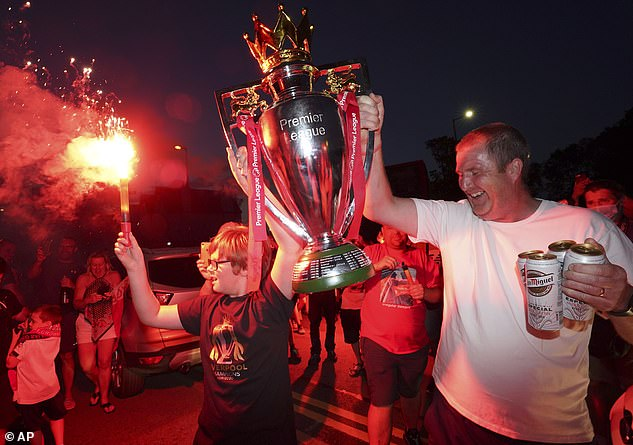 Liverpool fans hold aloft a replica Premier League title, which Jordan Henderson will now lift