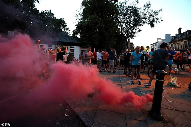 A flare is thrown into the street moments after Man City's loss confirmed Liverpool's title