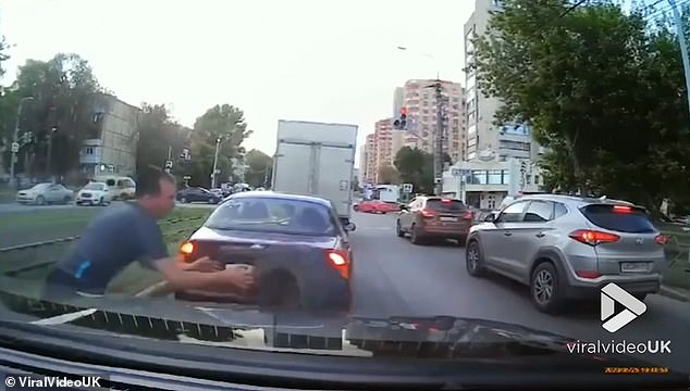 Dashcam footage captured the perfectly timed moment as he grabs the tyre just before it hit his car