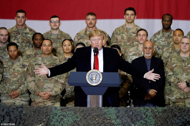 President Donald Trump delivers remarks to U.S. troops, with Afghanistan President Ashraf Ghani standing behind him, during an unannounced visit to Bagram Air Base, Afghanistan, November 28, 2019. A Russian military unit paid Taliban fighters bounties to kill American forces, according to the New York Times