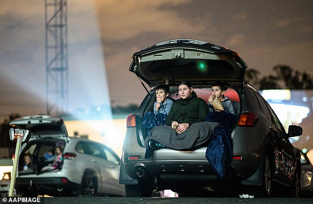 Car registration fees will be frozen in some states and territories as a result of the coronavirus crisis (pictured, a family watch a drive-through film in Blacktown on May 28)