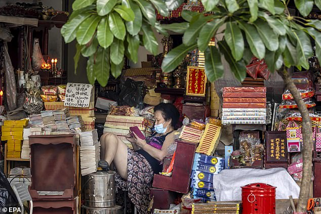 GUANGZHOU, CHINA: A woman wearing a mask sits in her boutique in Guangzhou, June 26, 2020. China is trying to contain a second wave of cases of coronavirus, which were found mainly in Beijing