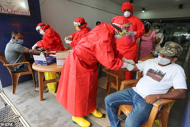 COLOMBO, SRI LANKA: Sri Lankan health workers wearing protective equipment perform COVID-19 blood tests and swab tests on shop workers in a local market in Colombo, Sri Lanka, June 26, 2020