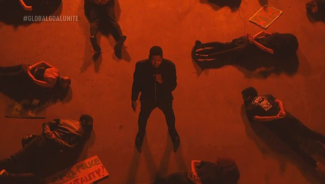 Torn from the headlines: at the end of the song, he crossed a scene in the middle of actors disguised as demonstrators lying face down, hands behind their backs.
