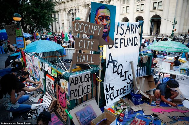 Protesters plastered signs and artwork on a subway entrance as they gathered at an encampment outside City Hall Friday