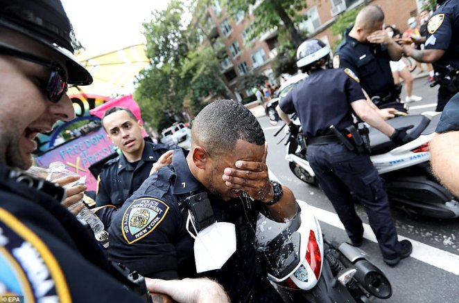 The officers doused their faces with water to get the pepper spray out of their eyes, assisted by their colleagues
