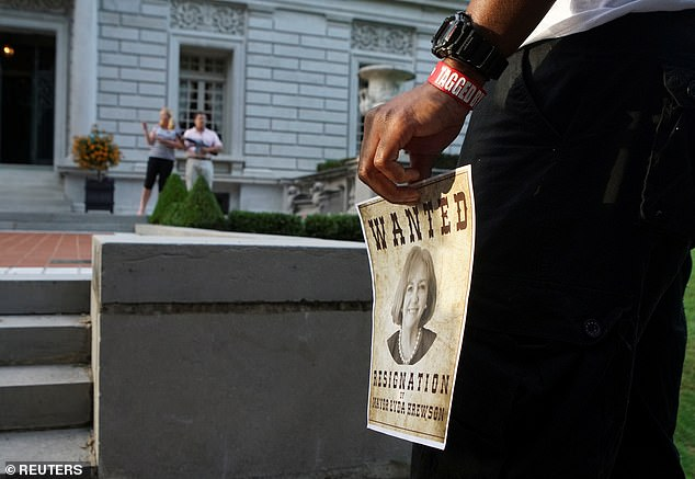 A protester holds a flyer calling for the resignation of St. Louis Mayor Lyda Krewson as a couple defend their home during a protest against the mayor