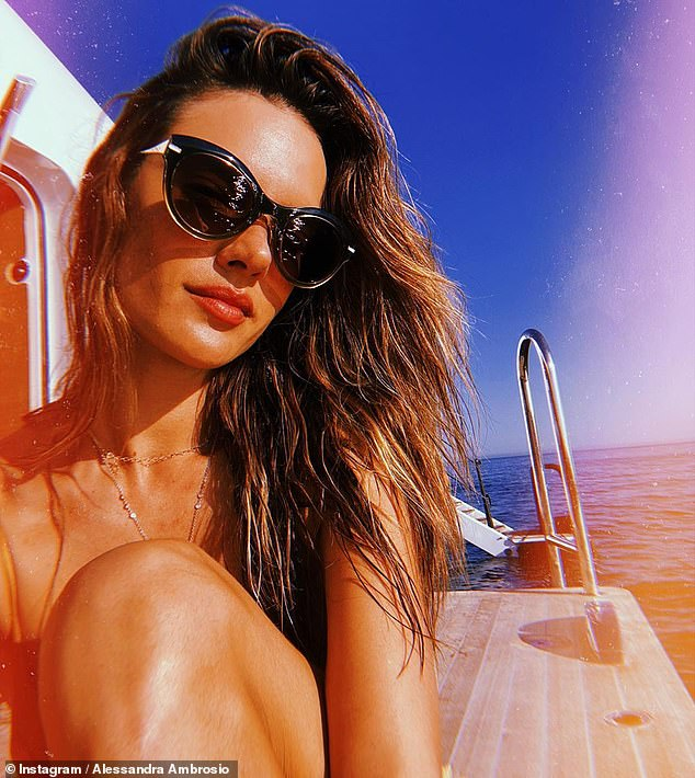 Turning heads: The former Victoria's Secret Angel highlighted her sensational figure as she relaxed in her tiny two-piece, which she styled with circular-framed shades by OMEGA