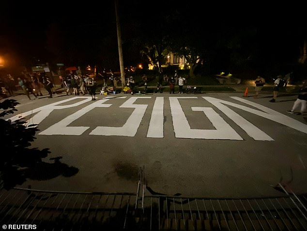The word 'resign' is seen painted on the street in front of Mayor Krewson's house in St. Louis