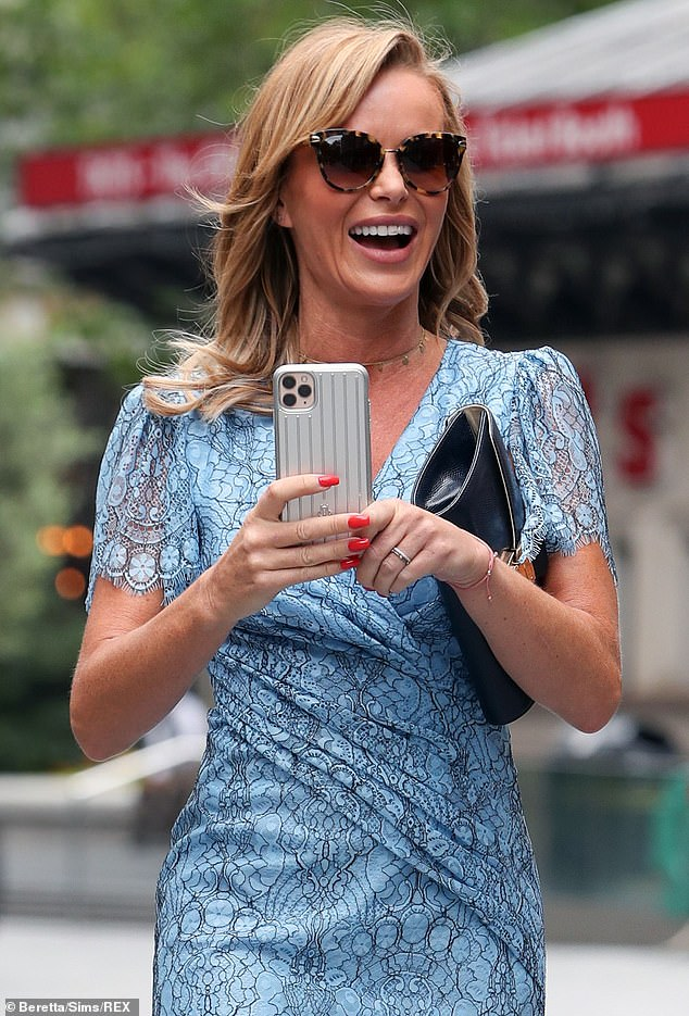 Smiles: The presenter appeared to be in good spirits as she laughed and held up her phone