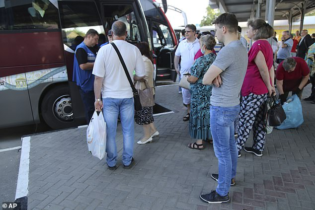 Over 220,000 Ukrainians living in areas held by Russia-backed rebels received Russian passports last year. Above,people observe social distancing guidelines to protect against coronavirus as they queue to get on a bus to Russia at a bus stop in Donetsk, eastern Ukraine