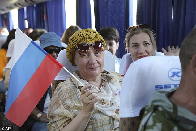 Russian authorities this month have gone to great lengths to lure voters to polling stations amid the coronavirus outbreak. Above,a woman holds a Russian national flag sitting on a bus to Russia at a bus stop in Donetsk, eastern Ukraine