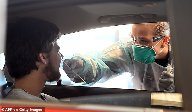 A Defence Force member tests a man for coronavirus on Monday. Australia's top scientists have urged people to wear facemasks and say Victoria may need targeted lockdowns