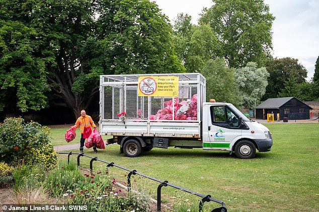 A council worker goes about emptying bins and removing rubbish from Christ's Pieces park in Cambridge