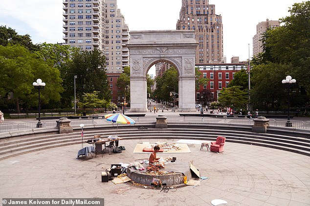 Mishefski reads in the middle of the fountain as New Yorkers enjoy a day at the park