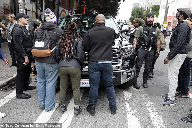 Instead he stayed inside the car, talking on the phone for most of the time, while his hired security stood outside the vehicle attempting to negotiate with protesters