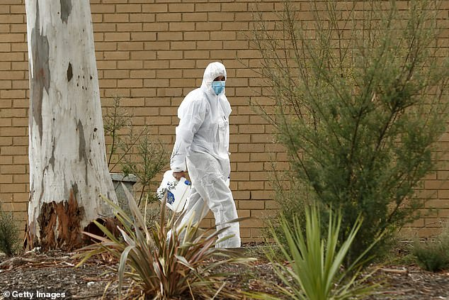 A cleaner leaves Keilor Views Primary School during contract tracing and cleaning after students tested positive for coronavirus