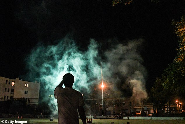 A spectator in Brooklyn watches on as the smoke clears after the end of the show