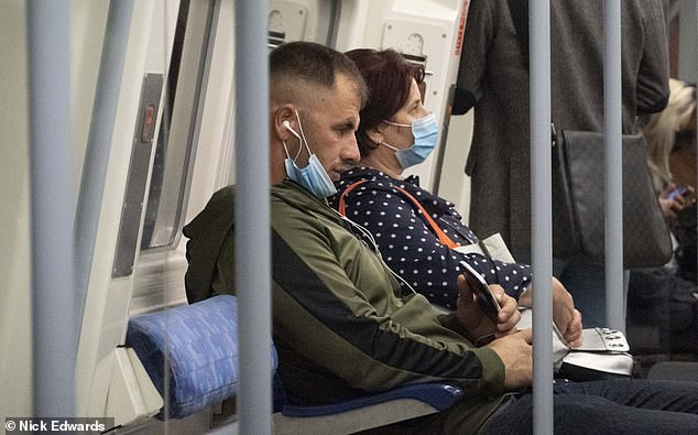 A man commutes with his mask below his mouth on a London Underground train this morning