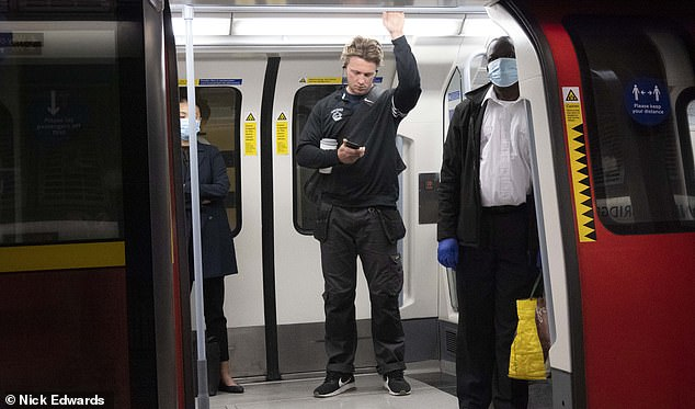 A man holds onto a handrail on a Jubilee line train this morning while not wearing a mask