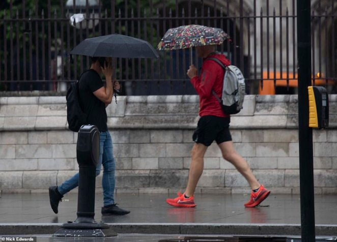 People walk under umbrellas through the rain in Westminster this morning as the capital experiences a wet start to the day