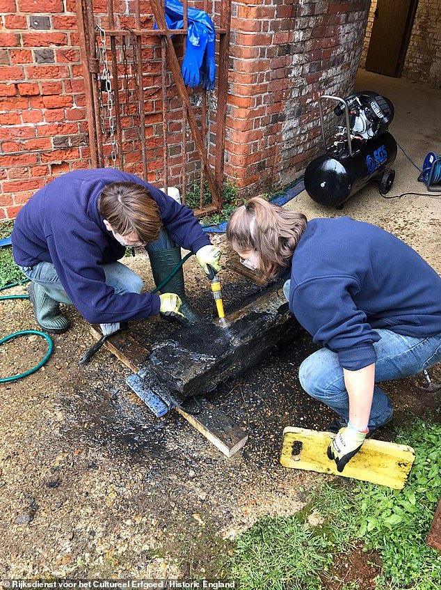 Many of the artefacts recovered from the wreck will now be examined in greater detail thanks to a £150,000 grant from the Wolfson Foundation to update Historic England's X-ray facilities. Pictured, researchers work on a chest of sabre blades recovered from theRooswijk