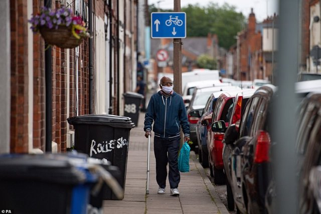 A man wearing PPE walks down a street in the North Evington area of Leicester, which has seen the most cases since mid-June