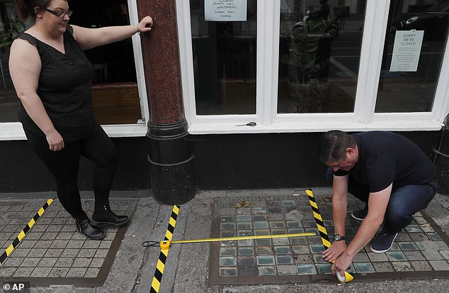 The 2m rule has been reduced to 'one metre plus' from this Saturday in a rule which officials hope will help hospitality businesses like pubs to reopen. Pictured: Employees outside a pub lay social distancing lines on the pavement outside in preparation for July 4