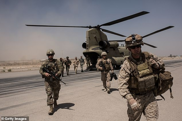 U.S. service members walk off a helicopter on the runway at Camp Bost on September 11, 2017 in Helmand Province, Afghanistan