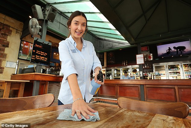 Bar worker Tessa Moore spays santizer onto a table at the Left Bank on June 06 in Fremantle