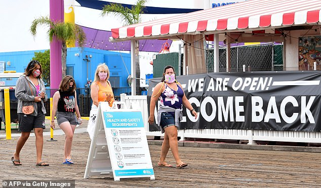 People wearing facemasks walk past a health and safety guideline board and an open restaurant on Santa Monica Pier, June 26, 2020 in Santa Monica, California