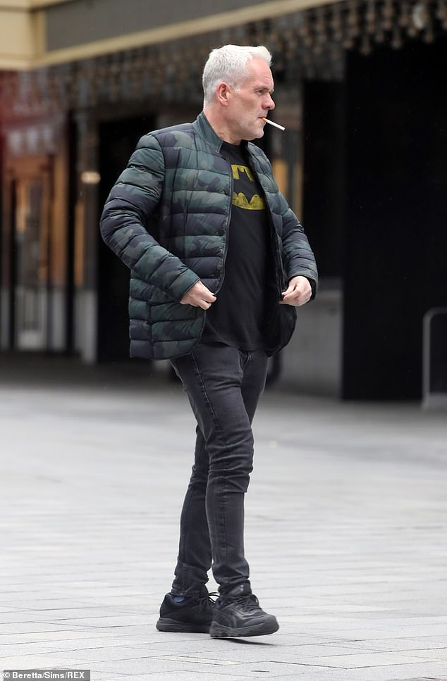 Health kick: Chris Moyles, 46, puffed on a cigarette in his Batman T-shirt following his five stone weight loss on Tuesday, after fearing he would be dead by 50