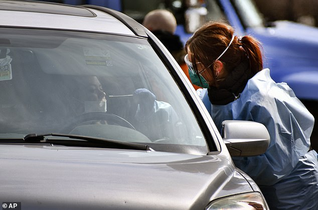 Just four states, Alaska, Hawaii, Montana and Vermont, are doing enough testing to suppress the virus. Pictured: Critical care nurse Molly Spaeny (right) with St Vincent Healthcare, swabs a patient for a coronavirus test in a drive-thru testing center outside the hospital in Billings, Montana, June 18